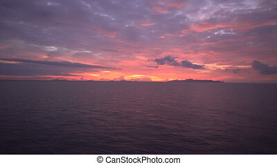 Beautiful sunset on waving sea, view from top deck of moving...