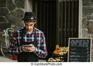 grocer with mobile phone at the entrance of their trade