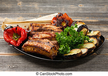 The meat and vegetables roasted on a grill with greens black...