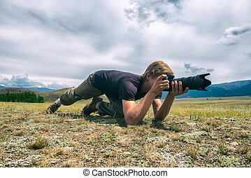 Close-up portrait photographer lying on the grass in mountains