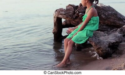 The little girl sitting on a log