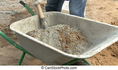 Manual wheelbarrow with concrete outofdoors.