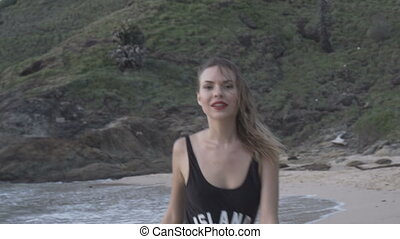 Pretty woman in black swimsuit at the beach
