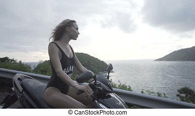 Pretty woman in black swimwear on the motor scooter