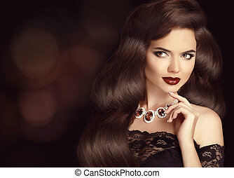 Elegant Brunette woman with long shiny wavy hair. Beauty...