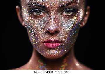 Portrait of beautiful woman with sparkles on her face. Girl...