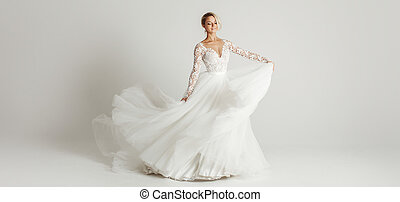 Beautiful attractive bride in wedding dress with long full...