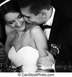 Fiance hugs bride's shoulder and smiles