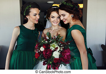 Bride reach out a bouquet while making fun with bridesmaids