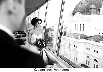 Bride looks thoughtful out of the window at cityscape
