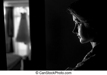 Bride stands thoughtfully in the dark room