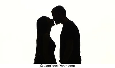 Portrait of two people kissing. Silhouette. White