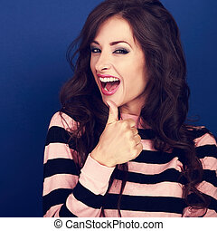 Excited smiling young woman showing thumb up sign with open mouth on blue background. Closeup portrait