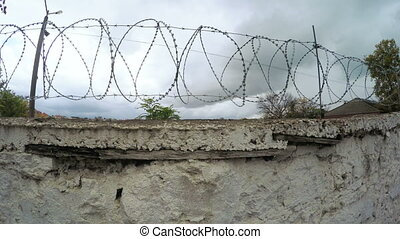Concrete fence with barbed wire - Panorama over prickly...