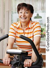 Spinning senior woman - Mature woman exercise on spinning...