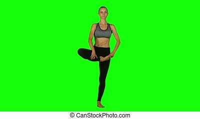 Girl is engaged in yoga on a background. Green screen
