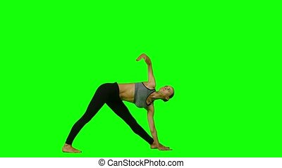 Woman doing yoga in sports clothes. Green screen