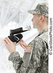 Indoors shot of American soldier holding VR glasses -...