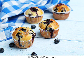 Tasty blueberry muffins on a blue wooden background