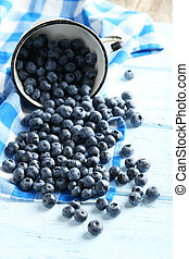 Blueberries in cup on a blue wooden background