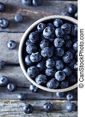 Blueberries in mug on a blue wooden background