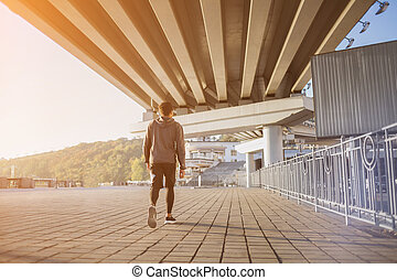Young fit man running at outdoors, autumn , attractive dark skinned runner jogging fast, sport concept