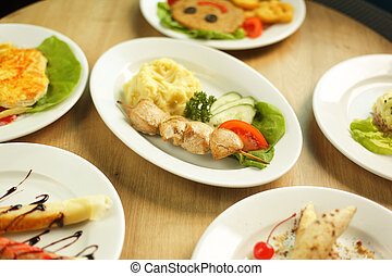wide variety of dishes on the table in the restaurant for children