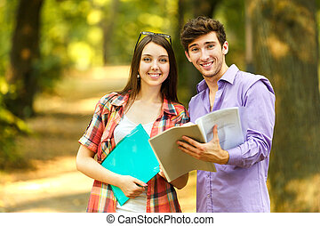 couple of happy students with books in the Park