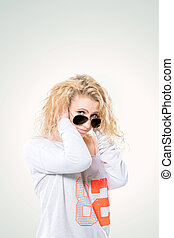 beautiful young blond woman in dark glasses and a white sweater on a white background