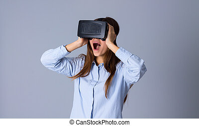 Woman using VR glasses - Amazed oung woman in blue shirt...