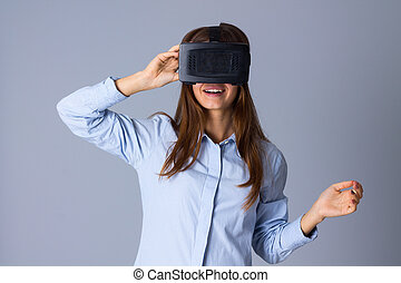 Woman using VR glasses - Happy young woman in blue shirt...