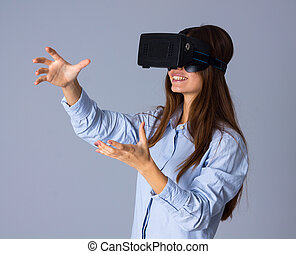 Woman using VR glasses - Young nice woman in blue shirt...