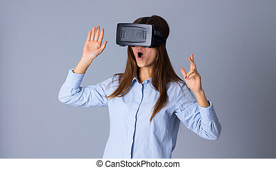Woman using VR glasses - Young amazed woman in blue shirt...