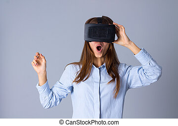Woman using VR glasses - Amuzed young woman in blue shirt...