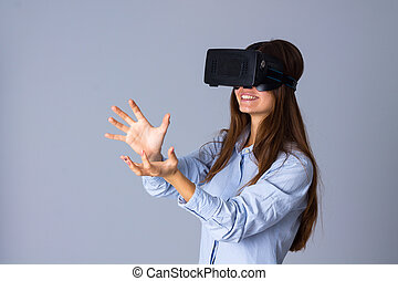 Woman using VR glasses - Young smiling woman in blue shirt...