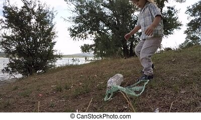 The little boy collects debris on the lake slow motion