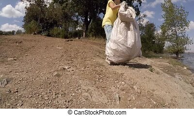 girl cleaning a park from trash, slow motion - Ecology,...