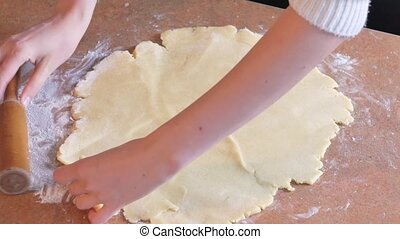 Baker kneading dough with rolling pin on table prepares...
