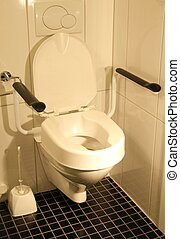 Handicap toilet - Toilet with raised seat and handle bars.