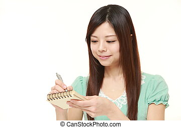 young Japanese woman writing in notebook - portrait of young...