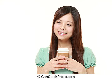 Japanese woman takes a coffee break - portrait of young...