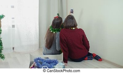 Two young girl preparing Christmas tree for decorations taking selfie having fun