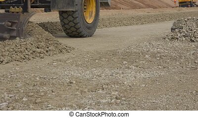 Grader machine leveling rubble stones on new road...