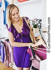 Young caucasian woman choosing a dress