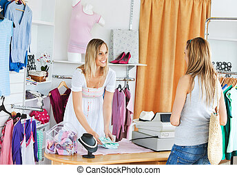 Attractive saleswoman packing clothes in a bag in a clothes...