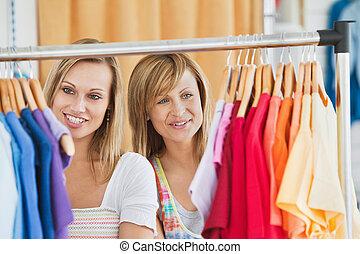 Beautiful female friends doing shopping choosing shirts