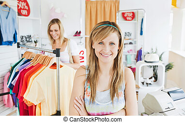 Delighted young woman smiling at the camera doing shopping with her friend standing in a clothes store