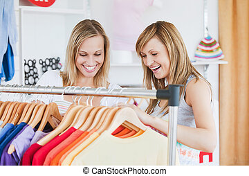 Pretty female friends doing shopping choosing shirts