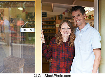 Portrait Of Couple Running Delicatessen Outside Store