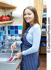 Teenage Girl With Part Time Job Washing Up In Coffee Shop